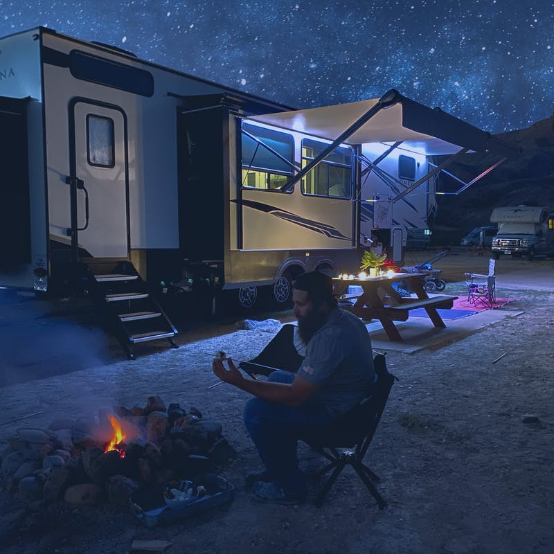 Sammy Seles's husband puts a marshmallow on a stick by a fire pit outside of their Keystone Montana under a starry sky.