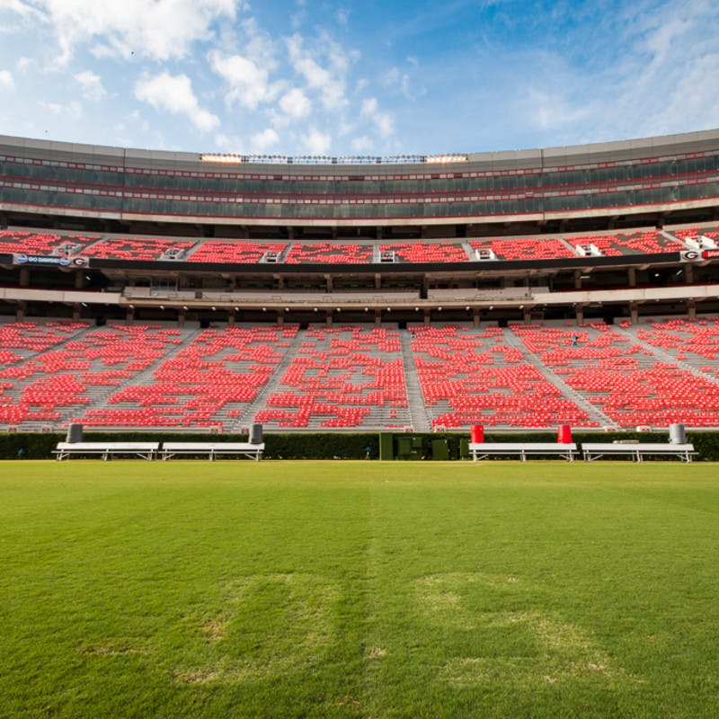 University of Georgia's Sanford Stadium in Athens, Georgia, view from the 50-yard line field, looking up at red seats and box seats.