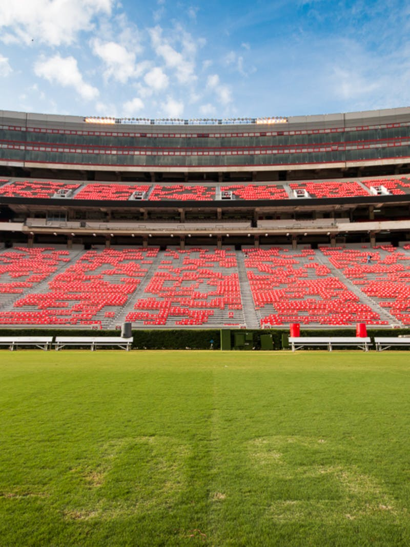Football stadium, with red seats, and a green field at the 50 yard line.