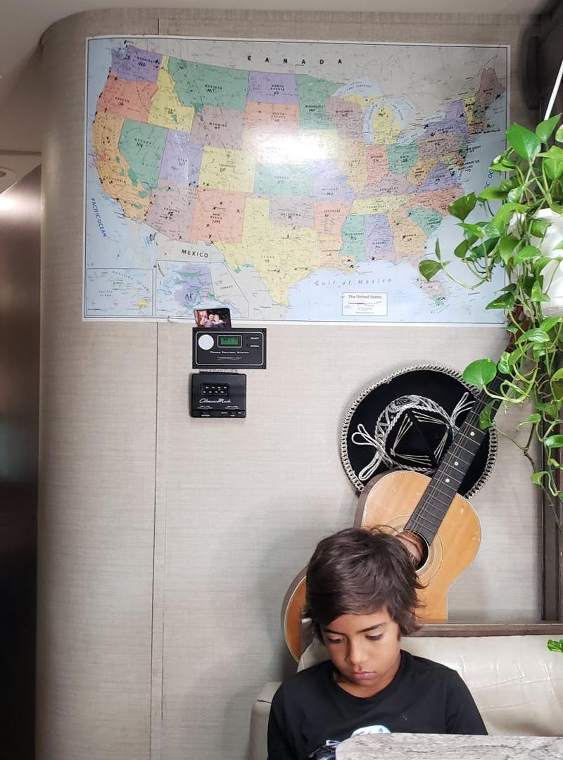 A map hangs on the wall inside of Sandra Peña's Class C RV near the kitchen table where her son sits.