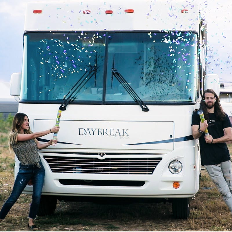 Bryce and Nellie Jurgy stand in front of the Class A motorhome, posing by windshield, popping streamers of colorful confetti into the air.