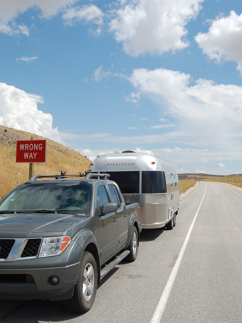 A car and an Airstream trailer parked on the side of a road on a beautiful day.