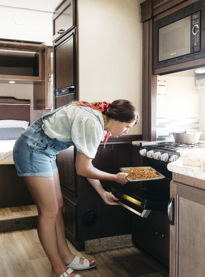 Sarah Glover adding putting the granola into the RV kitchen oven.