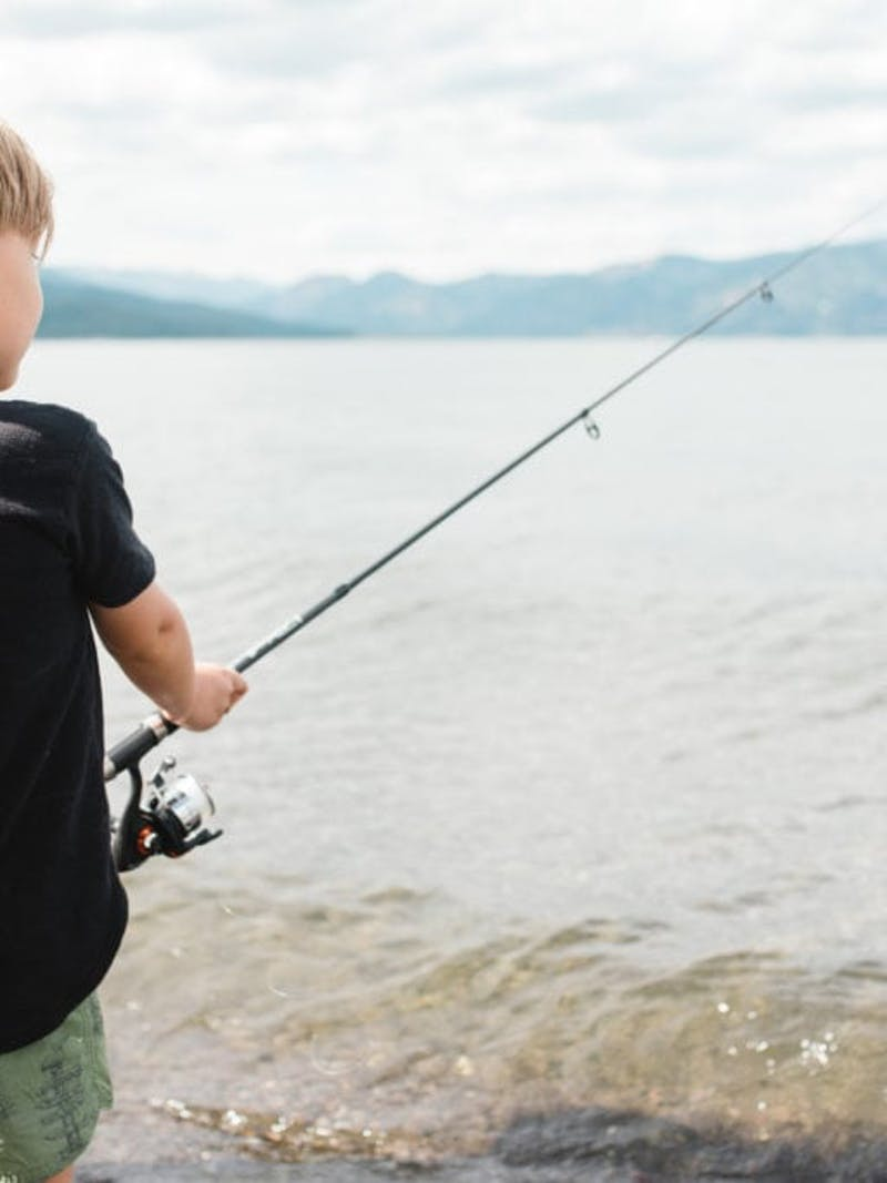 Young boy in black t-shirt holds fishing pole next to lake