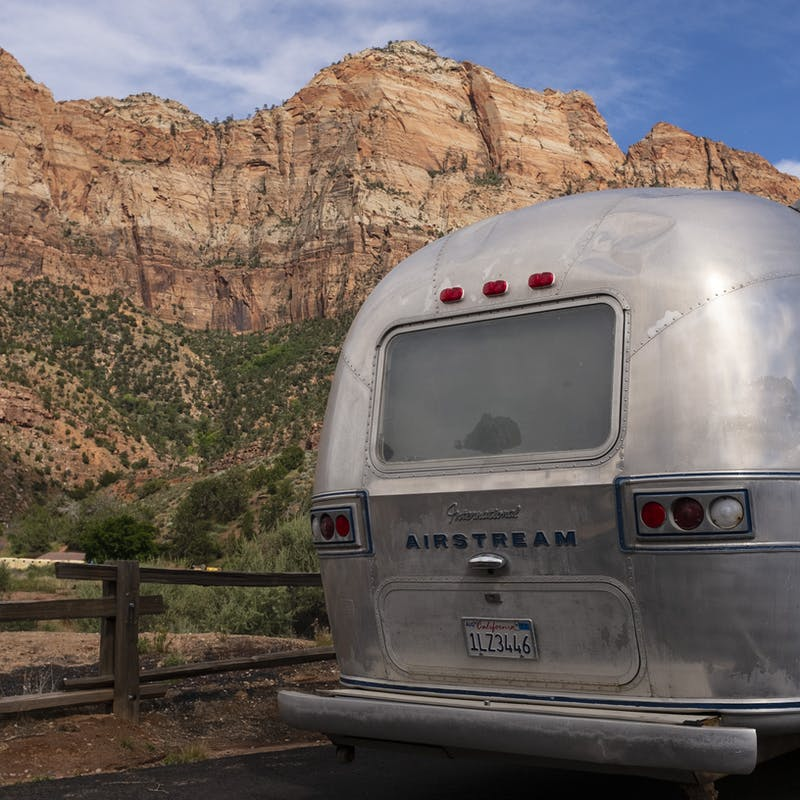 A shot of the family RV on the road, in front of red rock cliffs.
