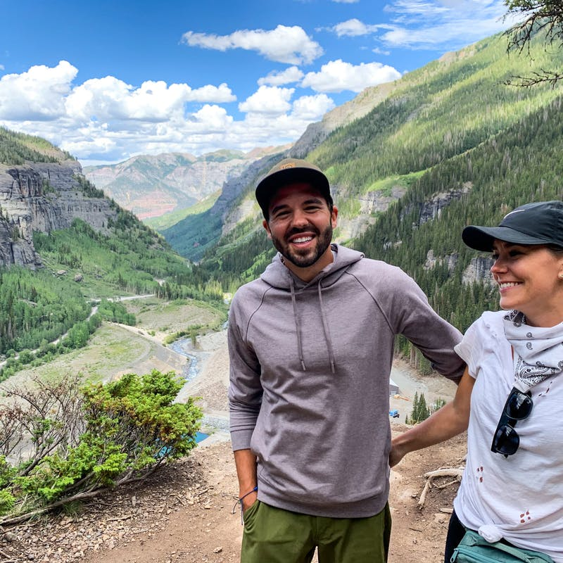 Jason and Dawn smiling for a photo on a ledge in a valley of mountains and trees.