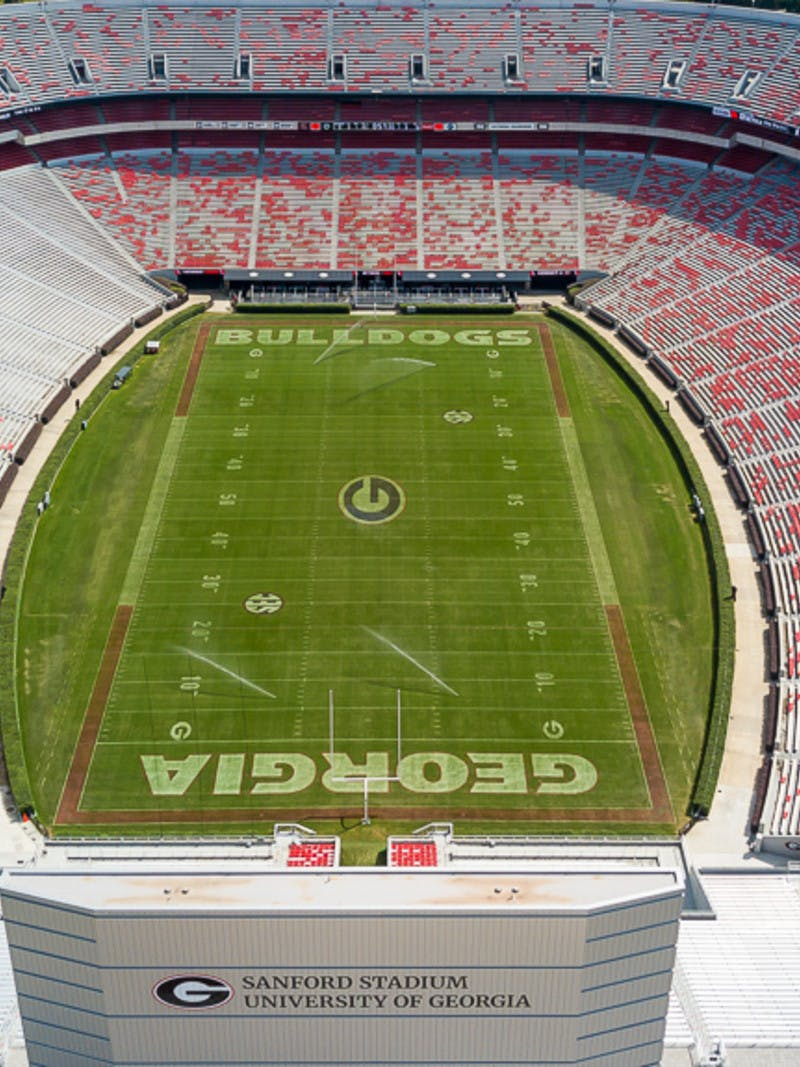 Aerial shot of University of Georgia's Sanford Stadium in Athens, Georgia, home of the Bulldogs, green football field with red seats in white bleachers.