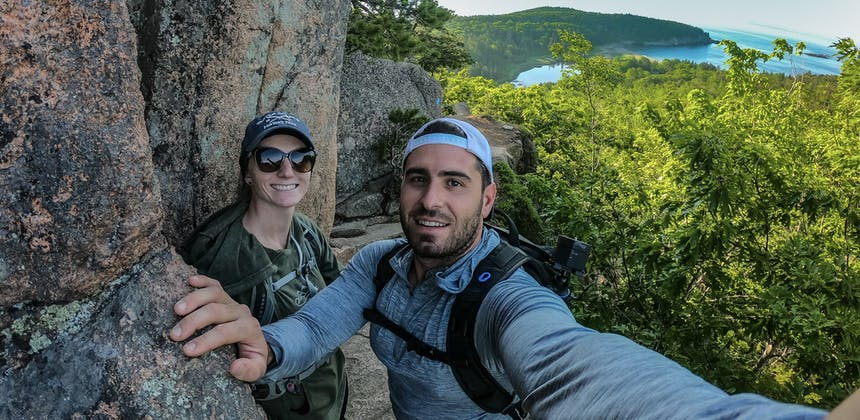 Jesse and Mel taking a selfie from the side of a rocky cliff, with a panoramic landscape in the background.