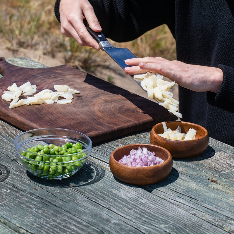 Small bowls on picnic table filled with chopped onion, water chestnuts, peas and cashews on a cutting board.