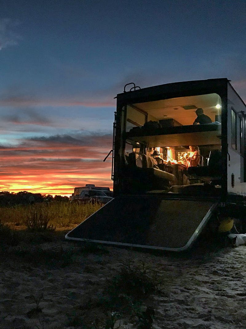 A rainbow sunset over a Toy Hauler RV that's glowing from within with light.