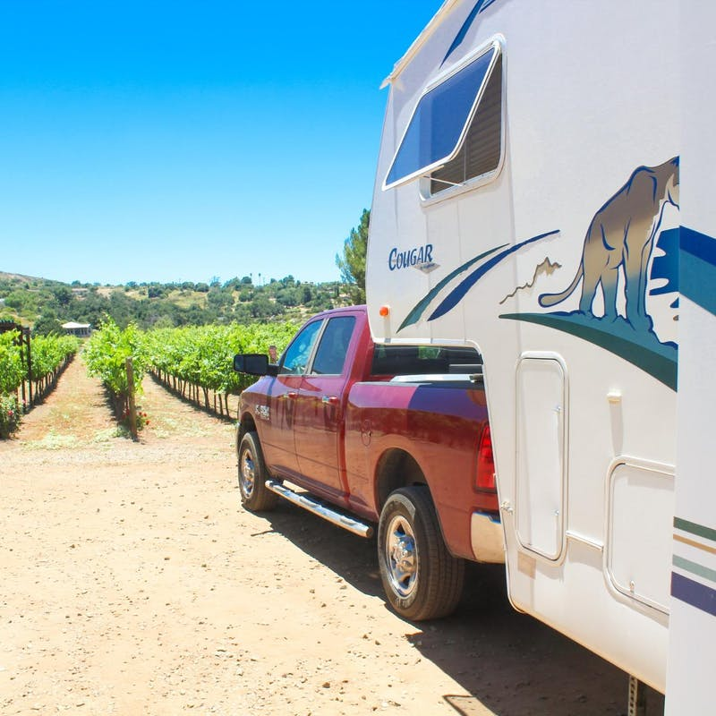 Jesse & Rachael Lyons park their Keystone Cougar RV in front of a vineyard.