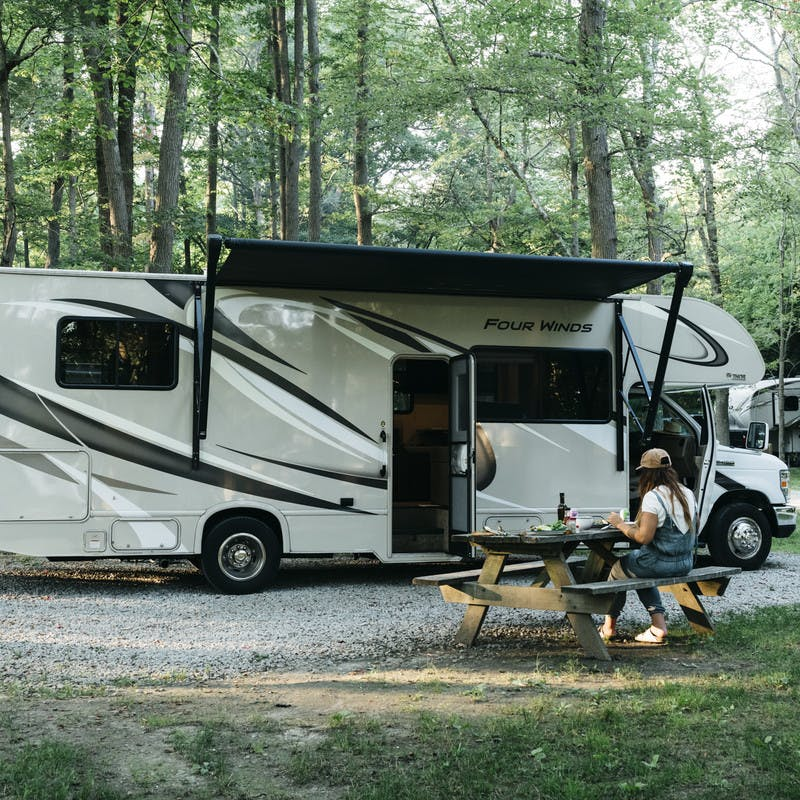 An RV at a tree-lined campground, parked with the awning up. Sarah sits at a picnic table nearby.