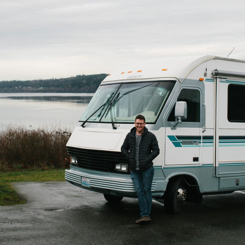 Jeffrey Shipley standing in front of his RV with a lake in the background.
