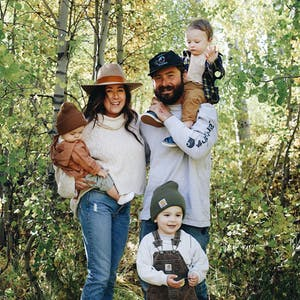 Autumn Bailey with her husband and three kids, posed for a picture amid green trees.