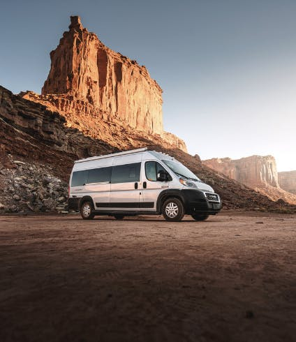 A class B RV parked near large rock formations in the desert.