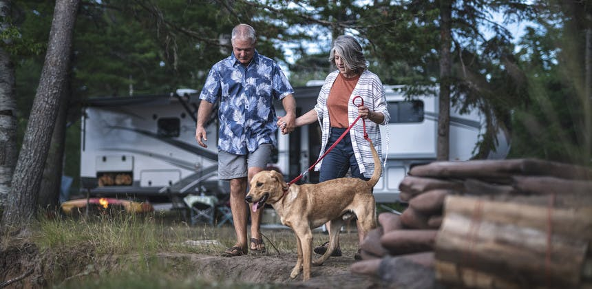 Older couple holding hands with dog walking away from fifth wheel RV in background
