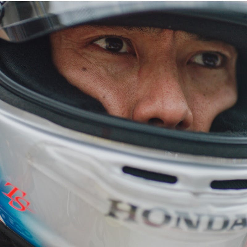 Takuma Sato puts on his helmet before getting into his race car at the 2019 Indy 500.