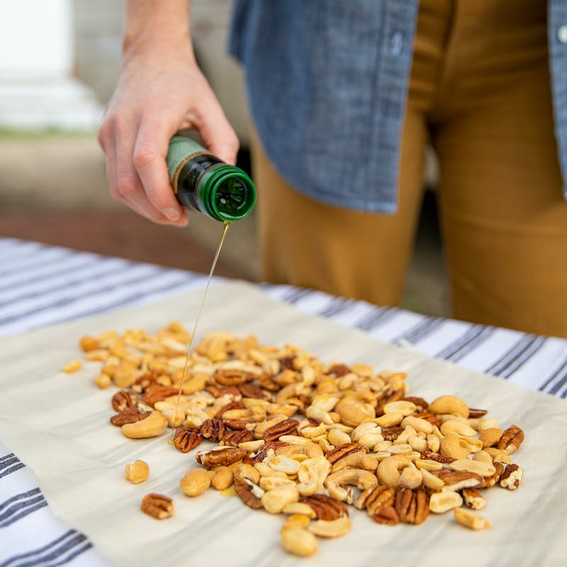 A hand drizzling oil over mixed nuts spread on parchment paper.