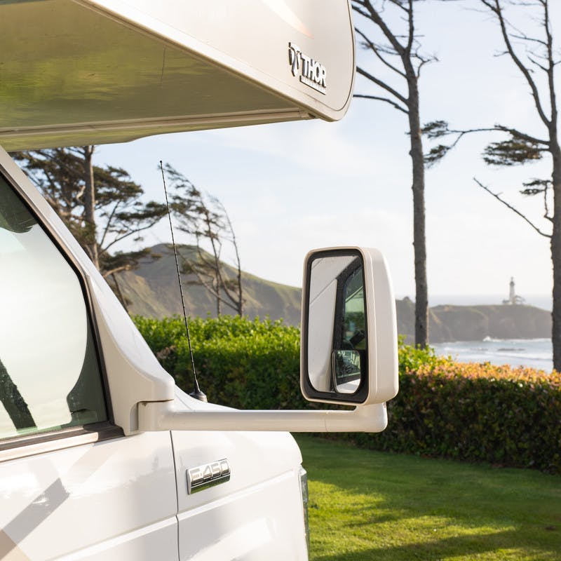 Front view of Class C motorhome looking out over grassy lawn and beach.