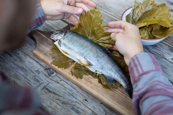 Hands wrapping full, stuffed trout in grape leaves, on a cutting board on a picnic table.