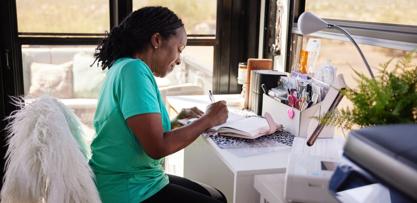 Robin sits at a desk and writes in a journal in the garage of their Keystone Fuzion toy hauler.
