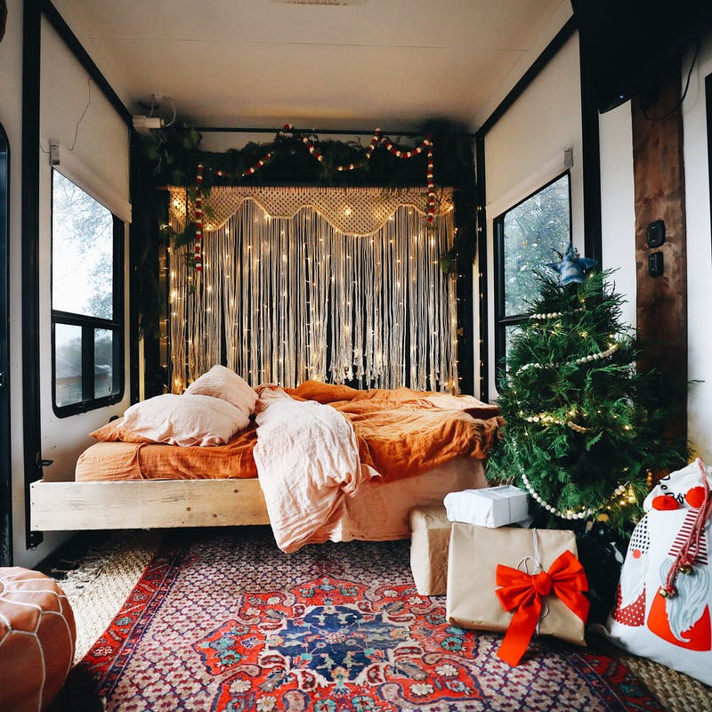 A small Christmas tree surrounded by gifts and lights, nestled in the master bedroom of an RV.