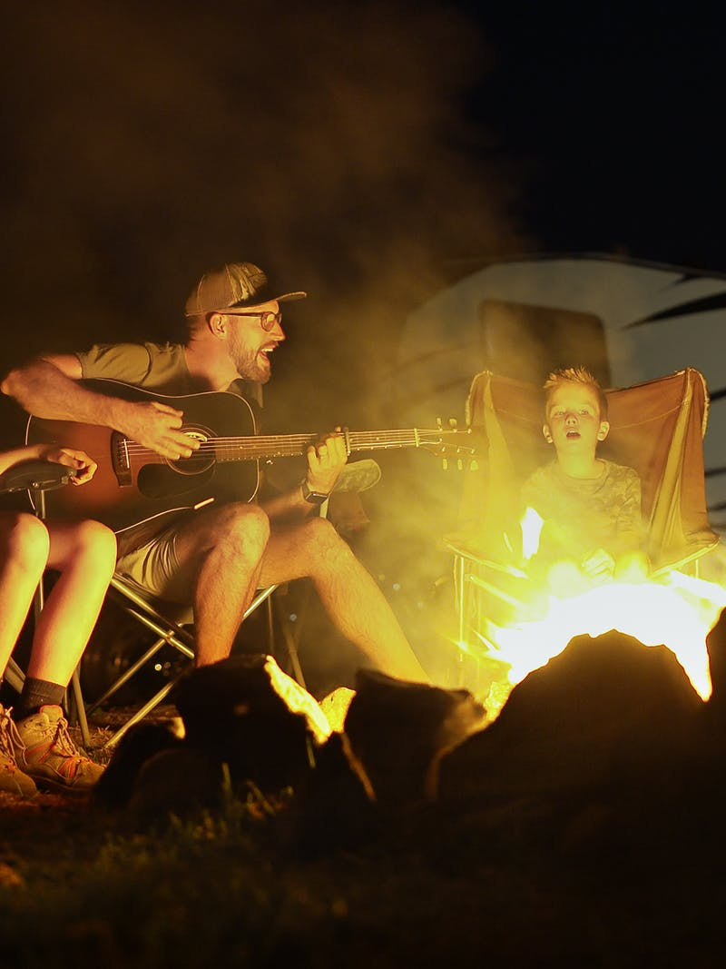 The Cutler family sings around a campfire.