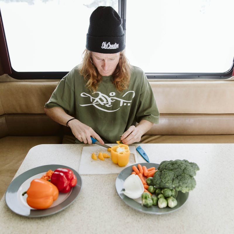 Ryan Barrick sits in Thor Class A motorhome chopping vegetables by snowy window.