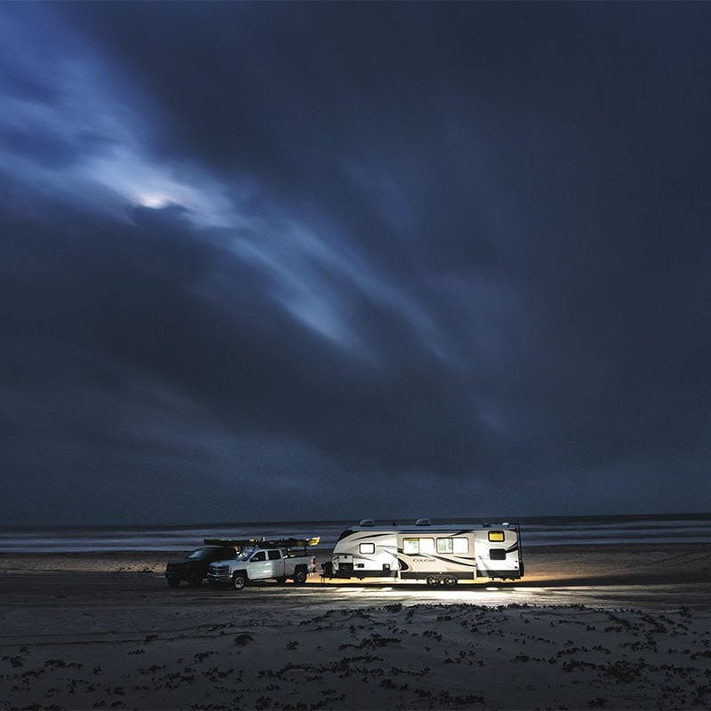 Keystone Cougar fifth wheel on the beach, lip up at night