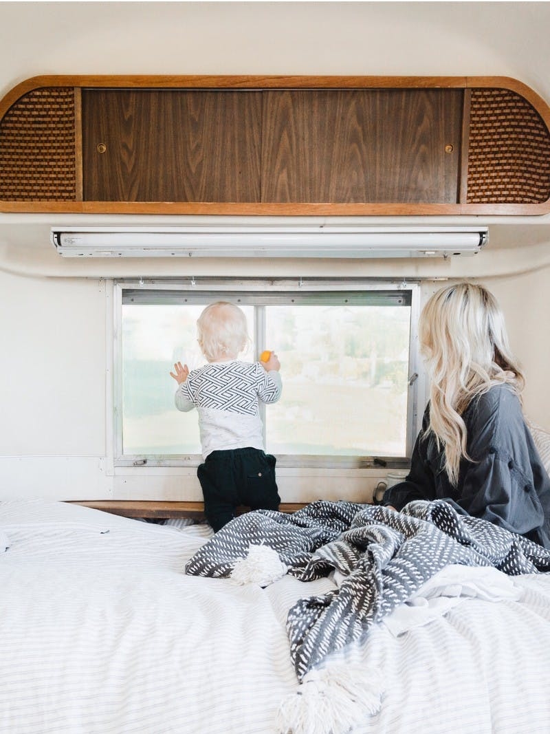 A blonde woman and a small blonde child snuggled in blankets in an RV bed, looking out the window at a beautiful view.