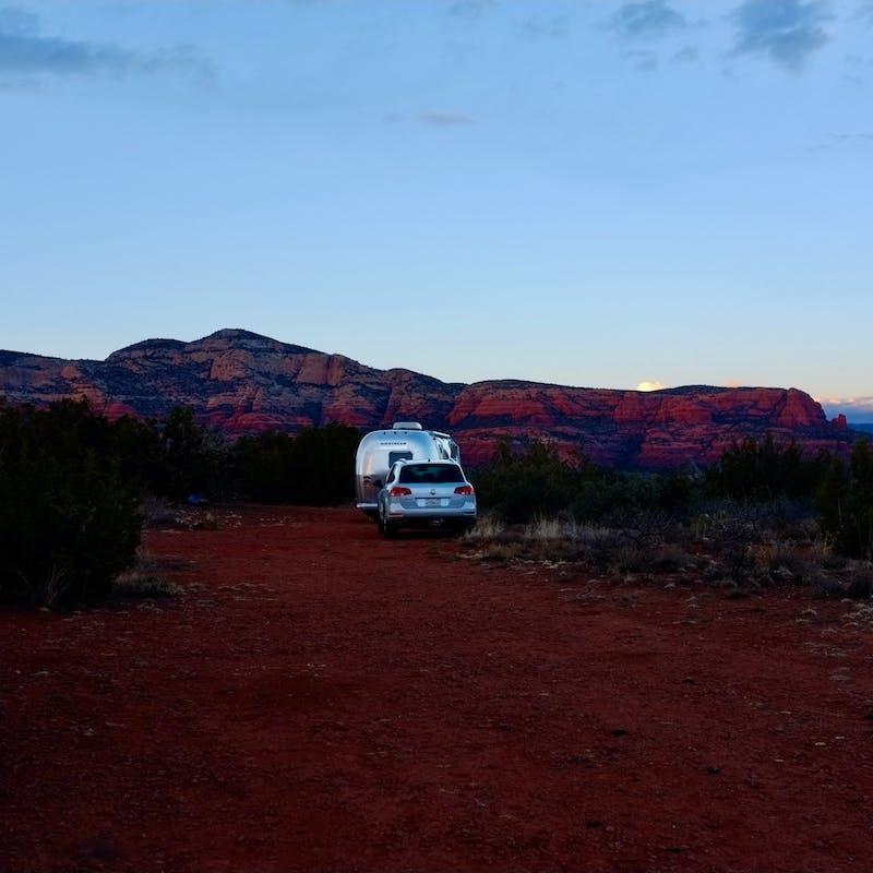 Dr. Na's RV parked at dusk in a desert landscape.