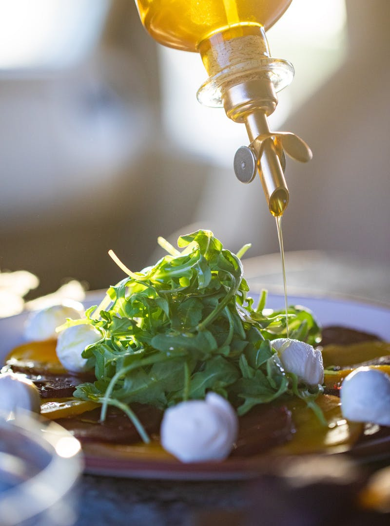 Close up of olive oil being poured onto a pile of arugula lettuce and small mozzarella cheese balls.
