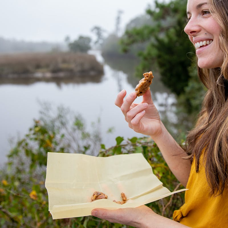 A woman smiling and eating a fresh praline candy.