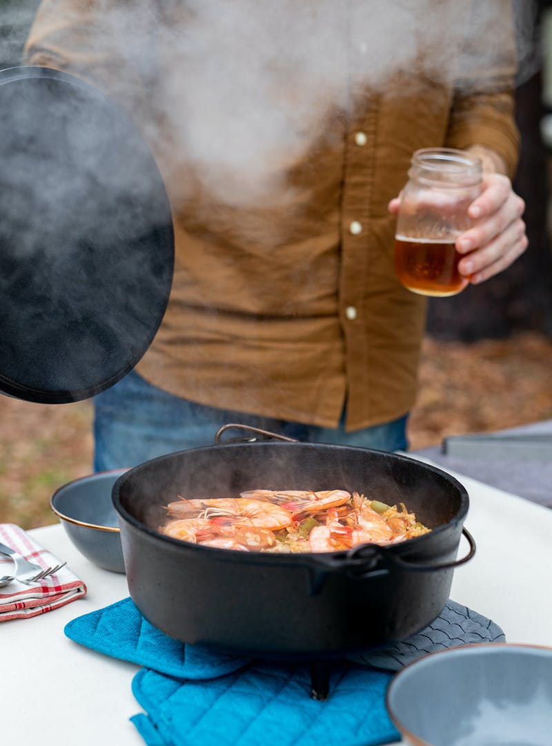 A steaming pot of jambalaya on a table.