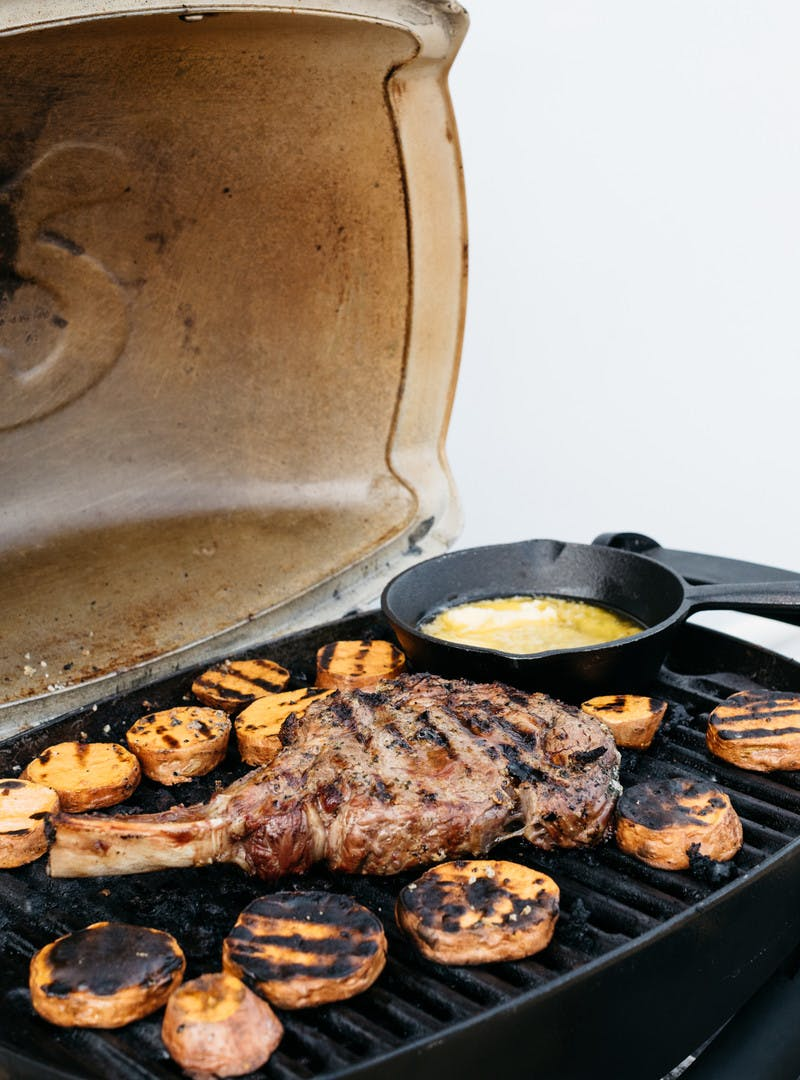 A steak with a long bone cooking on a grill alongside sweet potato rounds.