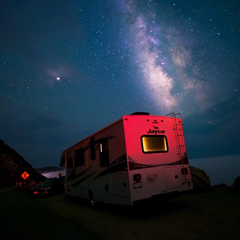 Sandra Peña's Jayco Class C RV parked under a starry sky in California.