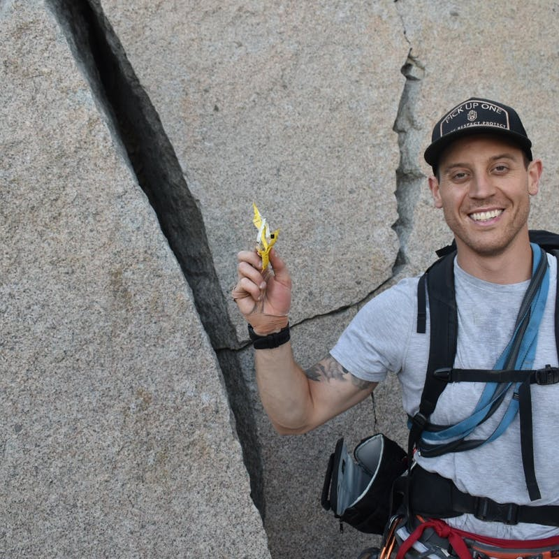 Male rock climber holding up trash in front of a boulder