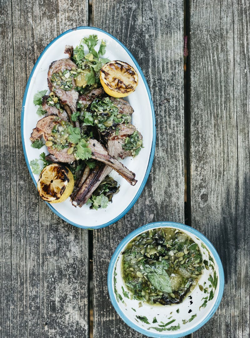 A finished shot of the grilled lamb and tomatillo sauce on a weathered picnic table background.
