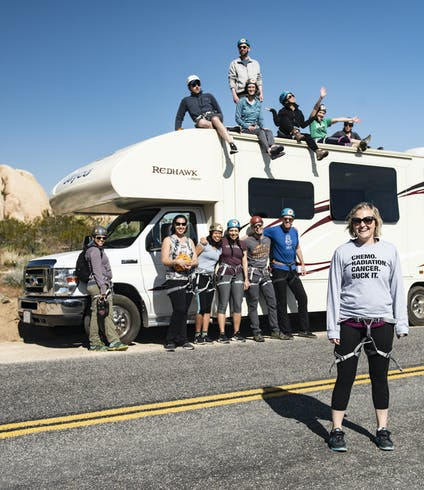 A group of First Descents participants stand together for a picture at a rock climbing excursion in Joshua Tree.