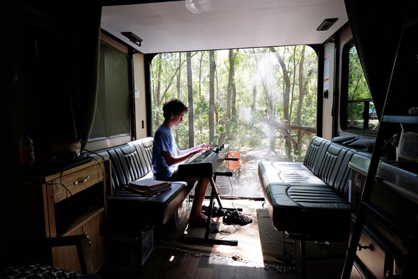 Gretchen Holcomb's son plays a keyboard in the garage of their Jayco Octane Toy Hauler.