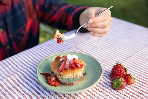 A uses a fork to scoop up a strawberry corn muffin.