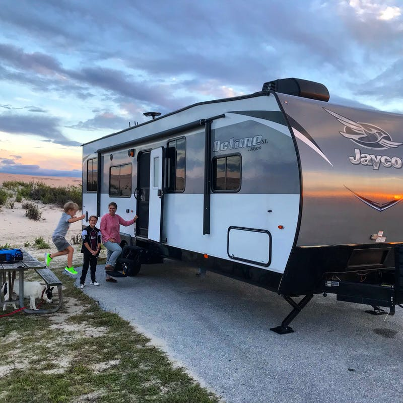 A woman and her kids going inside an RV.