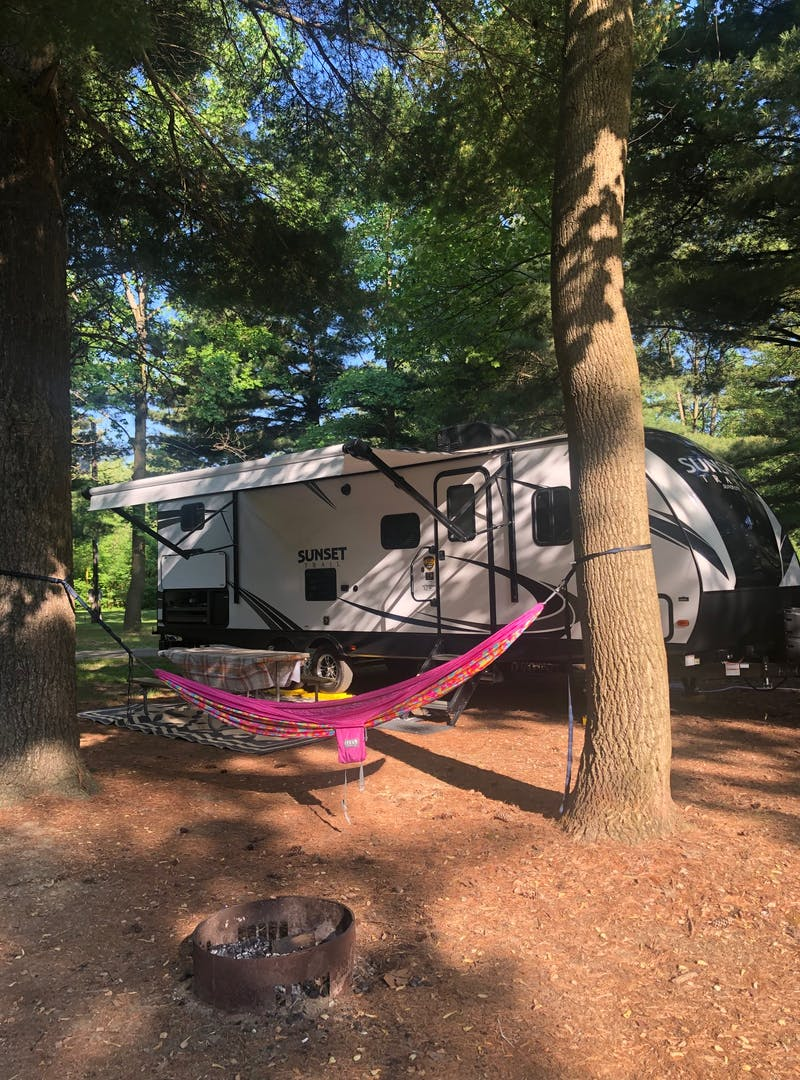 A sun dappled campsite with a hammock hung in front of an RV.