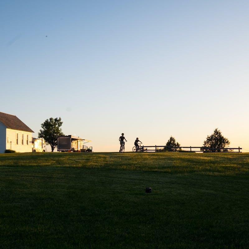 Gretchen Holcomb's kids ride their bikes in a prairie homestead where their RV is parked.