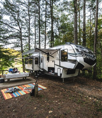 A fifth wheel rv parked at a campsite.