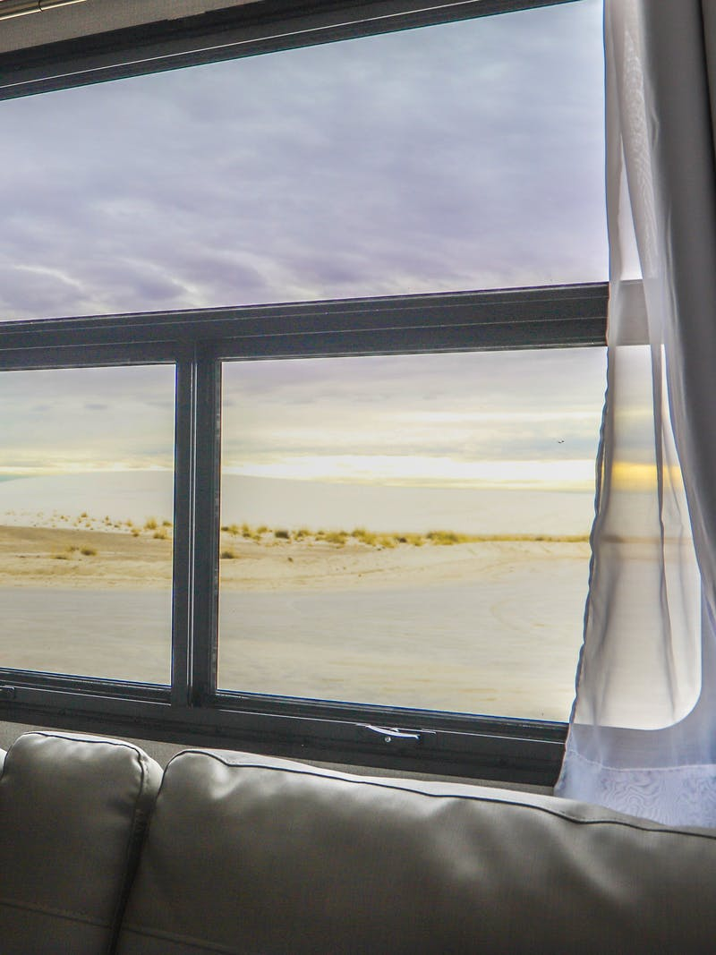 A view out an RV window to the sun setting over white sand dunes.