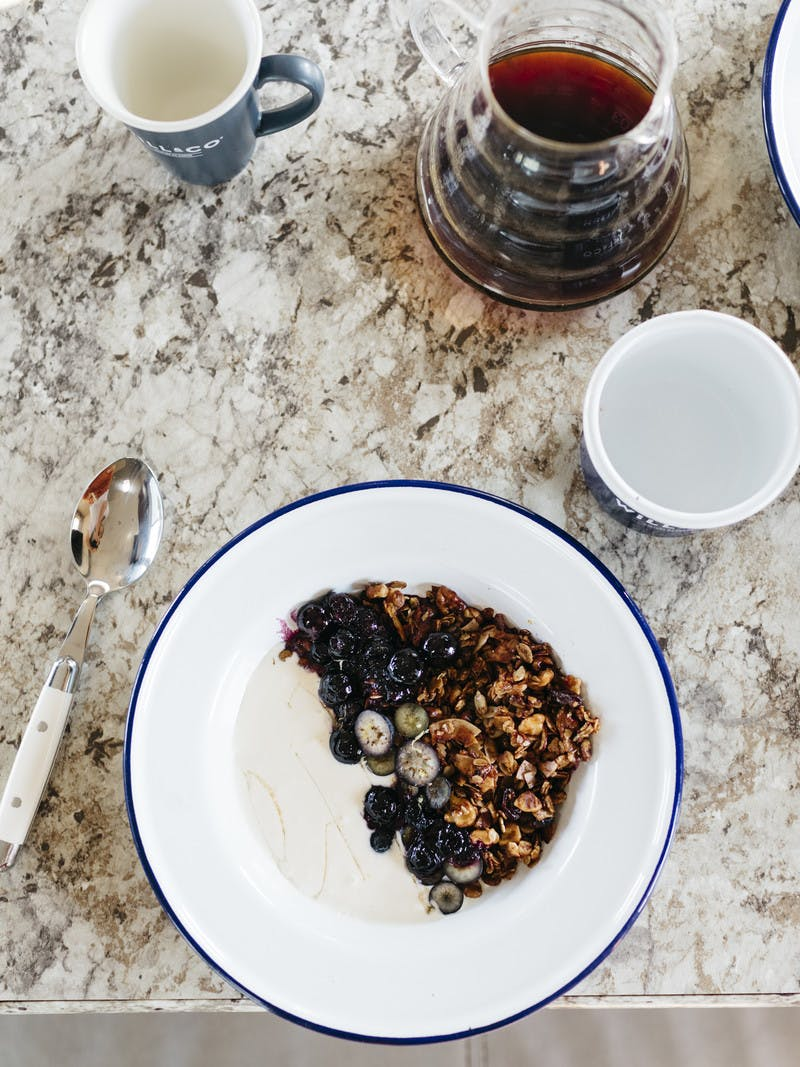 Bowl of hemp granola with blueberries on a tabletop.