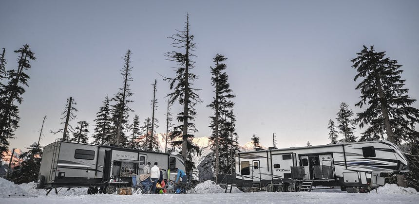 Two RVs stand side-by-side in the snowy mountains surrounded by trees.