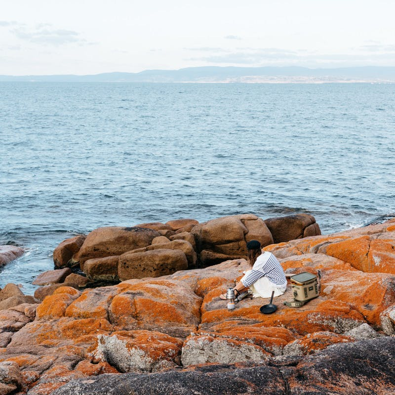 Sarah Glover from a distance, sitting on orange rocks with the ocean, preparing breakfast.