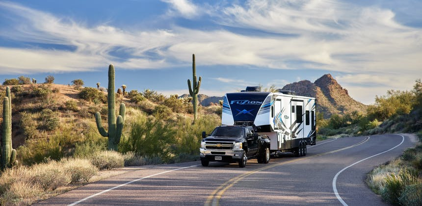 Robin and Warren towing their Keystone Fuzion on a windy desert road.